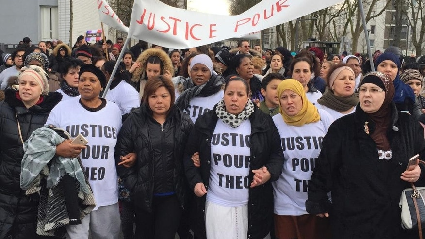 "People march in the streets of Aulnay-sous-Bois, north of Paris, France, holding a sign reading ""Justice for Theo"" during a protest, a day after a French police officer was charged with the rape of a youth, Monday, Feb. 6, 2017. One French police officer has been charged with raping a 22-year-old man and three others have been charged with assault after an identity check degenerated last week in the Paris suburb of Aulnay-sous-Bois. (AP Photo/Milos Krivokapic)"