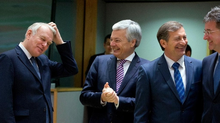 Belgian Foreign Minister Didier Reynders, second left, speaks with French Foreign Minister Jean-Marc Ayrault, left, during a meeting of EU foreign ministers at the EU Council building on Monday, Feb. 6, 2017. (AP Photo/Virginia Mayo)