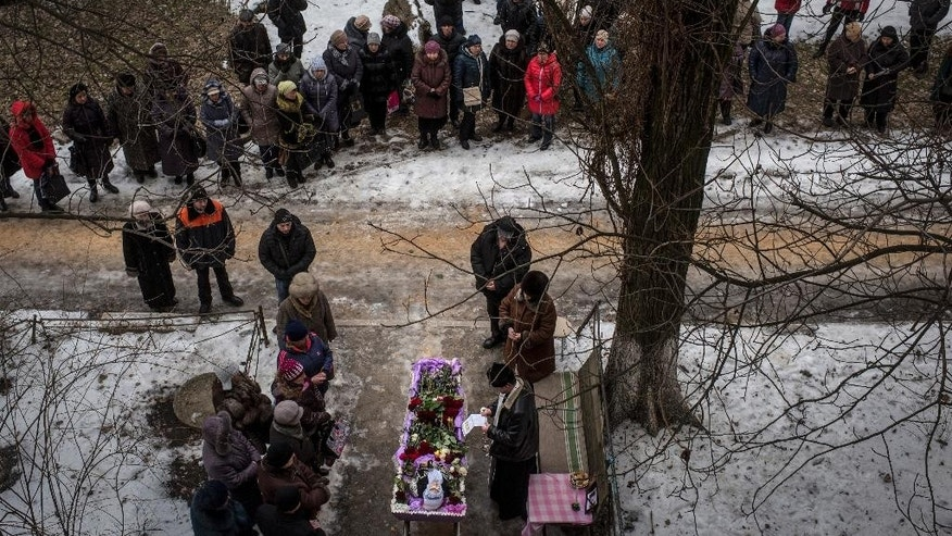 Relatives and friends of Elena Volkova, a victim of shelling, grieve at her funeral in Avdiivka, eastern Ukraine, Monday, Feb. 6, 2017. Fighting between government forces and Russia-backed separatist rebels has escalated over the past week in eastern Ukraine, killing at least 36 people, including civilians, and wounding dozens. (AP Photo/Evgeniy Maloletka)