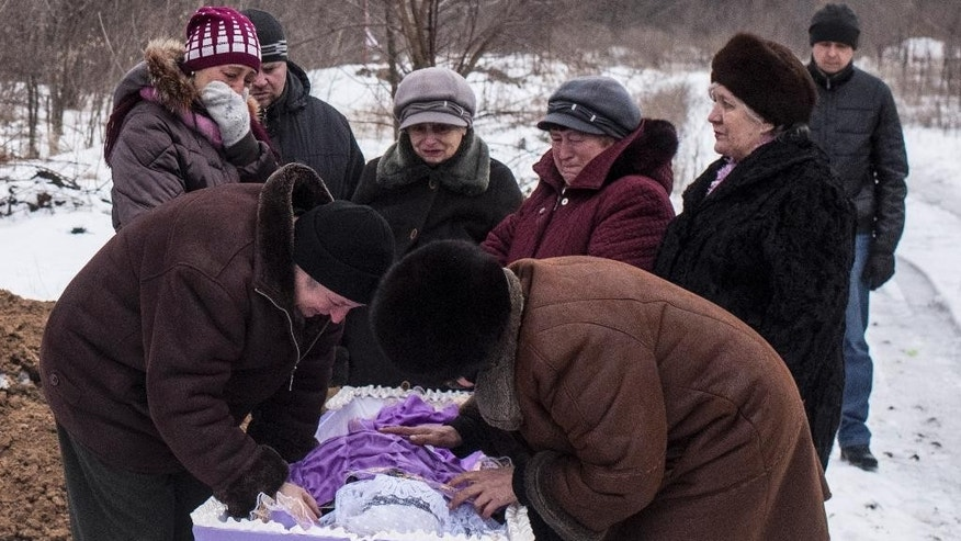 Relatives of Elena Volkova, a victim of shelling, grieve at her funeral in Avdiivka, eastern Ukraine, Monday, Feb. 6, 2017. Fighting between government forces and Russia-backed separatist rebels has escalated over the past week in eastern Ukraine, killing at least 36 people, including civilians, and wounding dozens. (AP Photo/Evgeniy Maloletka)