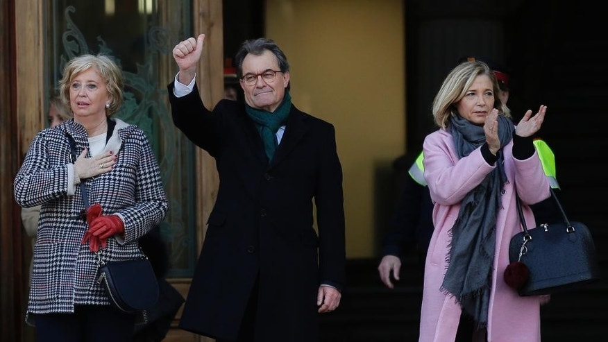 Former President of the Catalan regional Government Artur Mas, center, waves to the crowd as he arrives next to former Education Minister Irene Rigaua, left, and former Vice President Joana Ortega at the Catalonia's high court in Barcelona, Spain, Monday, Feb. 6, 2017. Thousands took the streets of Barcelona Monday to accompany the three Catalan politicians as they walked to a high court where they face charges for disobeying a Constitutional order two years ago banning a vote on the region's independence. (AP Photo/Manu Fernandez)