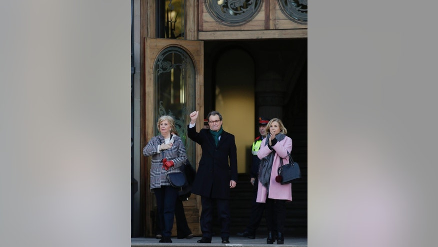 Former Catalan regional Government President Artur Mas, center, acknowledges the crowd as he arrives with former Education Minister Irene Rigaua, left, and former Vice President Joana Ortega at the Catalonia's high court in Barcelona, Spain, Monday, Feb. 6, 2017. Thousands have taken to the streets of Barcelona Monday to accompany the three Catalan politicians as they walked to a court where they face charges for disobeying a constitutional order two years ago banning a vote on the region's independence. (AP Photo/Manu Fernandez)