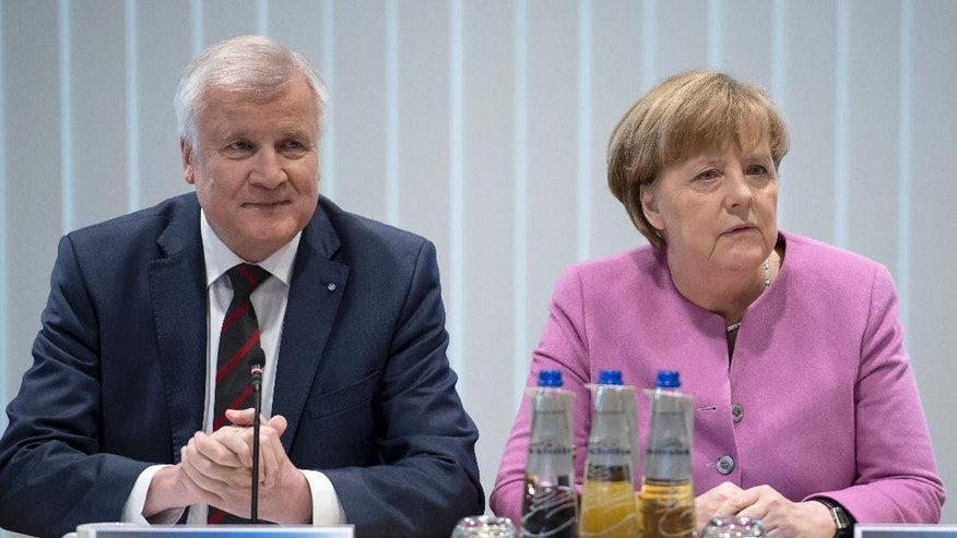Bavarian governor and head of the Christian Social Union party,  Horst Seehofer,  left, and German chancellor and head of the German Christian Democrats, Angela Merkel. attend a meeting  in Munich, southern Germany.   (Sven Hoppe/dpa via AP)