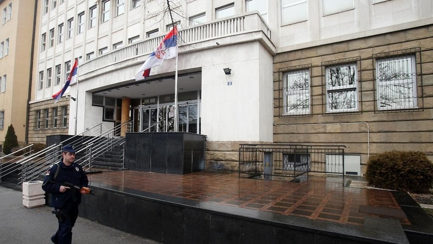 A police officer guards the entrance to the special court building during a trial of eight men accused of taking part in the massacre on the outskirts of Srebrenica, in Belgrade, Serbia, Monday, Feb. 6, 2017. Eight former Bosnian Serb special police troops went on trial Monday in Serbia charged with taking part in the massacre of thousands of Muslims in Srebrenica in 1995. (AP Photo/Darko Vojinovic)