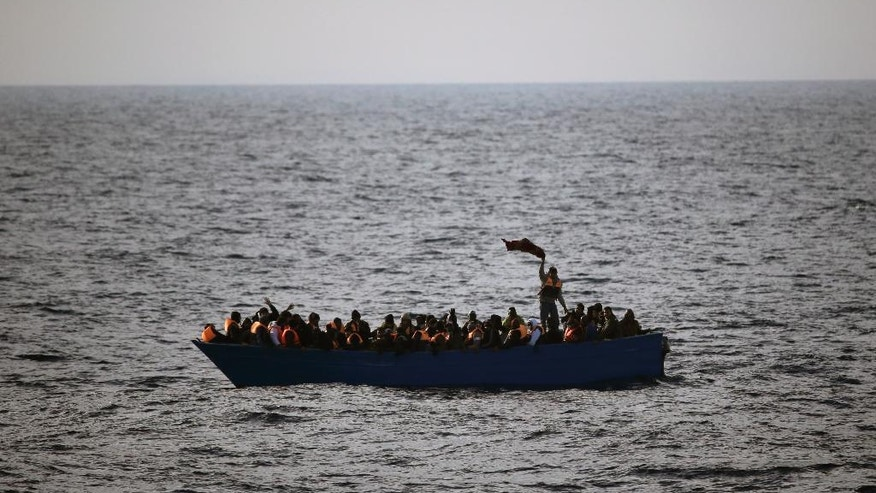 Migrants and refugees wave for help from inside a wooden boat 21 miles north of Sabratha, Libya, on Friday, Feb. 3, 2017. European Union leaders are poised to take a big step on Friday in closing off the illegal migration route from Libya across the central Mediterranean, where thousands have died trying to reach the EU, the EU chief said. (AP Photo/Emilio Morenatti)