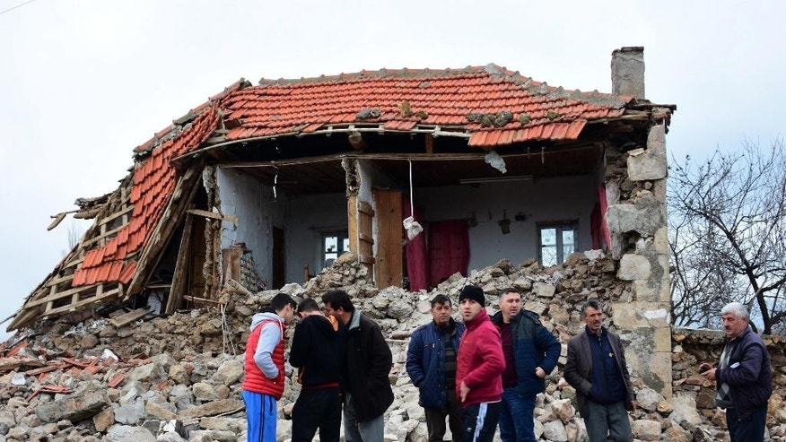 Villagers stand in front of a damaged house after two quakes, both with preliminary magnitudes of 5.3, jolted Turkey's northern Aegean coast, in Yukarikoy village Canakkale province, Monday, Feb. 6, 2017, damaging dozens of homes in at least five villages and injuring several people.(Mustafa Suicmez/DHA-Depo Photos via AP)