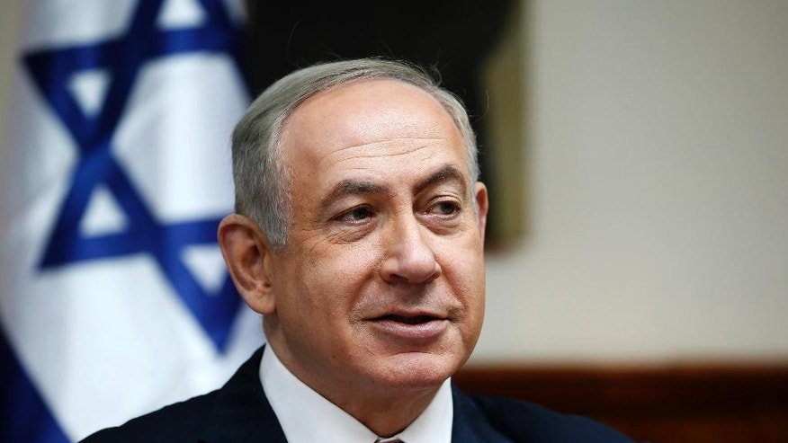 "FILE - In this Sunday, Jan. 22, 2017, file photo, Israeli Prime Minister Benjamin Netanyahu attends the weekly cabinet meeting in Jerusalem. Israel's prime minister is moving ahead with a contentious law that would legalize dozens of settlement outposts in the West Bank, despite questions about the bill's legality and a warning from the White House that settlement construction ""may not be helpful."" (Ronen Zvulun/Pool Photo via AP, File)"