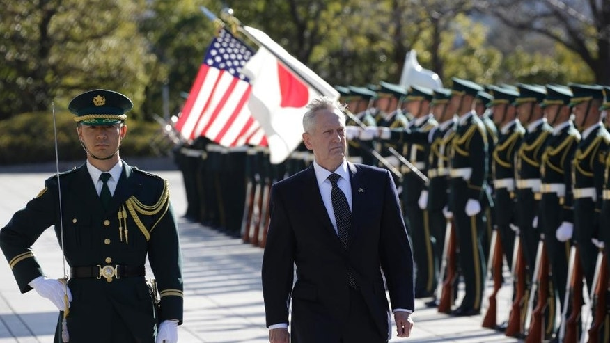 In this Saturday, Feb. 4, 2017 photo, U.S. Defense Secretary Jim Mattis, right, is escorted to inspect an honor guard at Defense Ministry in Tokyo. Mattis on Friday reassured two key U.S. treaty allies, South Korea and Japan, that President Donald Trump, who has raised doubts about the value of such partnerships, is fully committed to defending them. (AP Photo/Eugene Hoshiko, File)