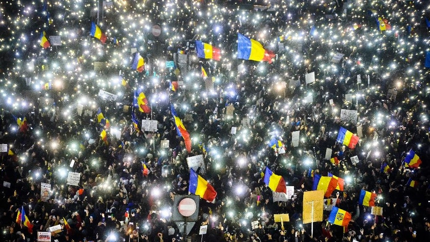 Tens of thousands of people shine lights from mobile phones and torches during a protest in front of the government building in Bucharest, Romania, Sunday, Feb. 5, 2017. Romania's government met Sunday to repeal an emergency decree that decriminalizes official misconduct, a law that has prompted massive protests at home and widespread condemnation from abroad. (AP Photo/Andreea Alexandru)