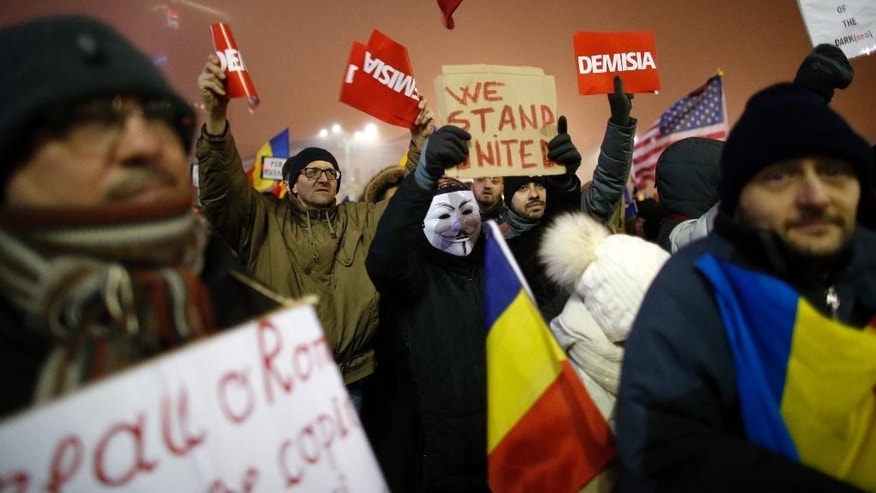 People shout slogans during a protest in Bucharest, Romania, Monday, Feb. 6, 2017. The leader of Romania's ruling center-left coalition said Monday the government won't resign following the biggest demonstrations since the end of communism against a measure that would ease up on corruption. (AP Photo/Darko Bandic)