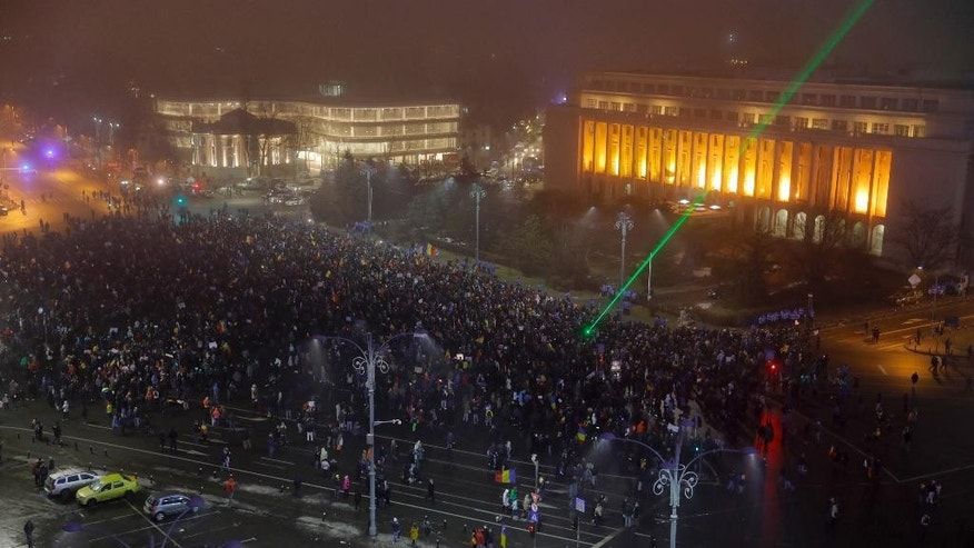 People gather for a protest in Bucharest, Romania, Monday, Feb. 6, 2017. The leader of Romania's ruling center-left coalition said Monday the government won't resign following the biggest demonstrations since the end of communism against a measure that would ease up on corruption. (AP Photo/Vadim Ghirda)