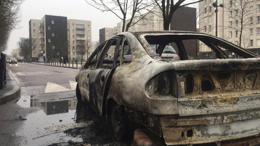 The remains of a car burnt by protesters on Monday night, in Aulnay-sous-Bois, north of Paris, France, Tuesday, Feb. 7, 2017. French police say over 20 protesters were detained during an eruption of violence against police in the Paris suburbs in which a police car was torched. The violence in the night of Monday to Tuesday is a show of outrage in support of a young black man who authorities allege was sodomized by a police officer's baton last week during a police operation that targeted drug traffickers. (AP Photo/Alex Turnbull)