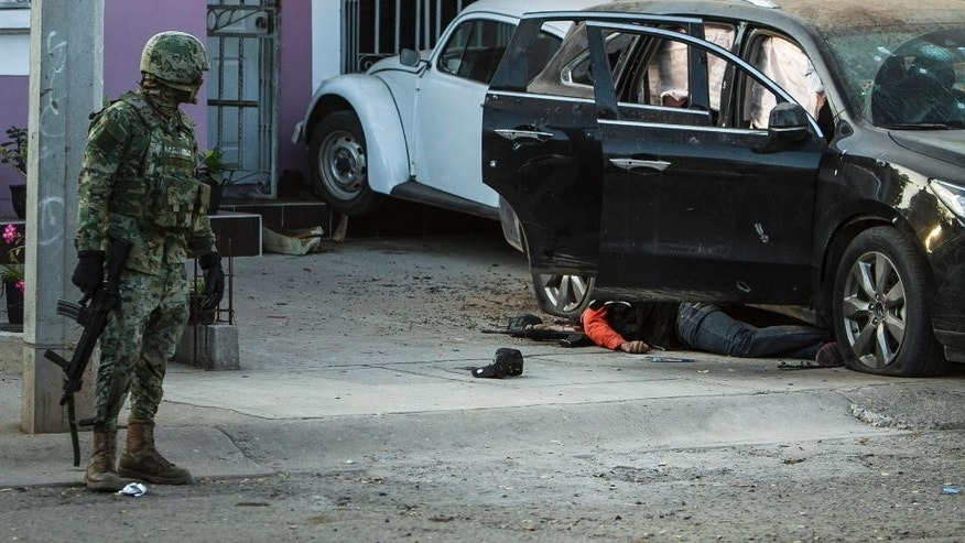 A Mexican marine looks at the body of a gunman as it lies next to a vehicle after a gun fight in Culiacan, Mexico, Tuesday, Feb. 7, 2017. The Sinaloa state prosecutor's office said in a statement that several suspects and a marine died in the early morning clash after the heavily armed men attacked the marines while on patrol in the city. (AP Photo/Rashide Frias)