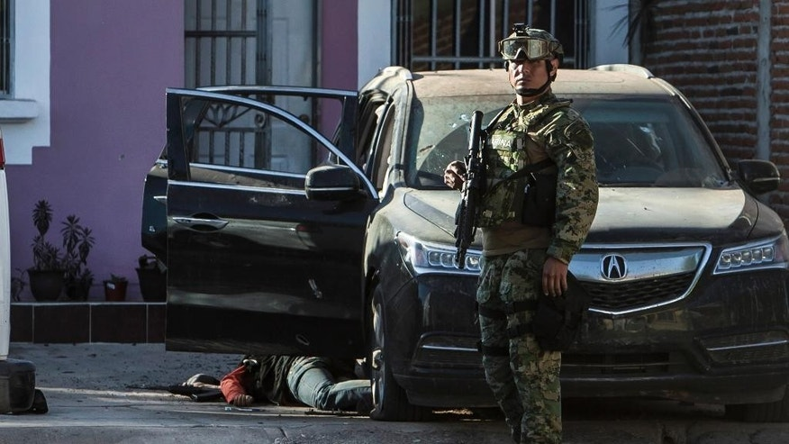 A Mexican marine stands close to the body of a gunman as it lies next to a vehicle after a gun fight in Culiacan, Mexico, Tuesday, Feb. 7, 2017. The Sinaloa state prosecutor's office said in a statement that several suspects and a marine died in the early morning clash after the heavily armed men attacked the marines while on patrol in the city. (AP Photo/Rashide Frias)