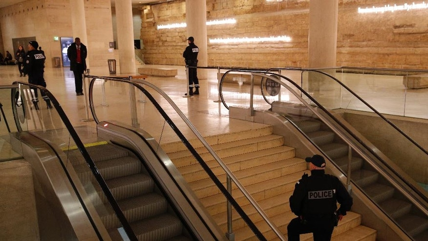 "Police officers patrol inside the Louvre Museum after a shooting outside at the museum in Paris, Friday Feb. 3, 2017. A knife-wielding man shouting ""Allahu akbar"" attacked French soldiers on patrol near the Louvre Museum Friday in what the president called a terrorist attack. (AP Photo/Christophe Ena)"