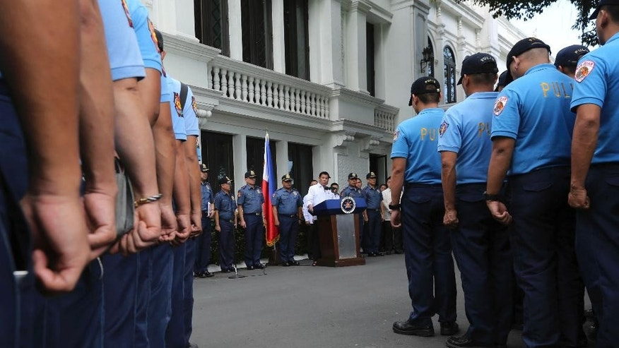 "In this photo provided by the Presidential Photographers Division, Malacanang Palace, Philippine President Rodrigo Duterte, center by the podium, speaks to erring policemen during an audience at the Presidential Palace grounds in Manila, Philippines, Tuesday, Feb. 9, 2017. Duterte angrily berated more than 200 allegedly erring policemen and said he would send them to a southern island to fight extremists dreaded for their beheadings. Duterte's expletive-filled outburst against the officers at the palace was his latest tirade against a police force that he has called ""rotten to the core."" He recently banned the national police from carrying out his anti-drug campaign after a group of officers used the crackdown as a cover to kidnap and kill a South Korean man in an extortion scandal. (King Rodriguez/Presidential Photographers Division, Malacanang Palace via AP)"