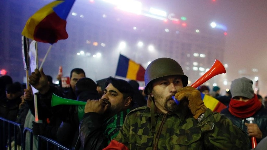 Protesters blow horns during a protest in Bucharest, Romania, Monday, Feb. 6, 2017. The leader of Romania's ruling center-left coalition said Monday the government won't resign following the biggest demonstrations since the end of communism against a measure that would ease up on corruption. (AP Photo/Darko Bandic)
