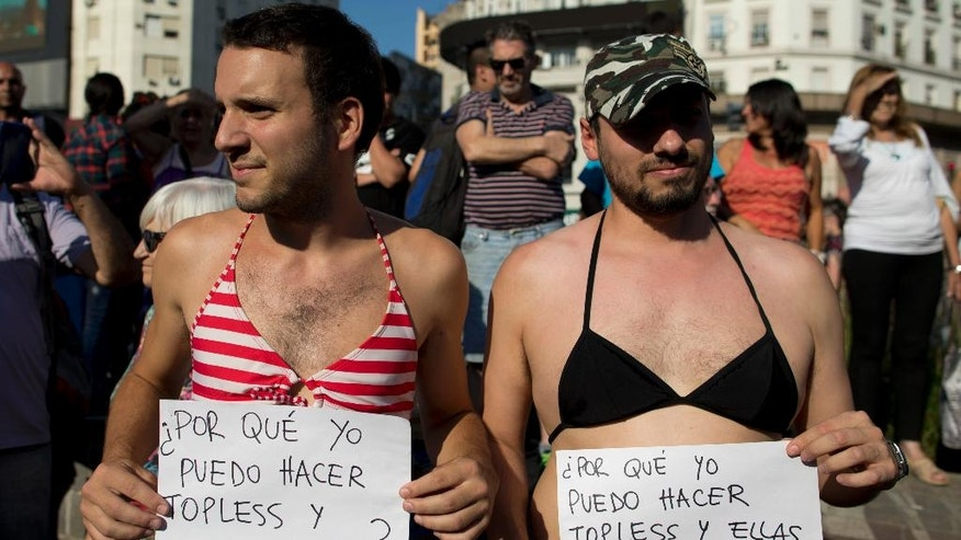 "Men in bikini tops hold signs that read in Spanish ""Why can I go topless and they can't"" during a bare-breasted demonstration in Buenos Aires, Argentina, Tuesday, Feb. 7, 2017. People protested after police threatened several weeks ago to detain several women sunbathing topless on a beach in Argentina. (AP Photo/Natacha Pisarenko)"