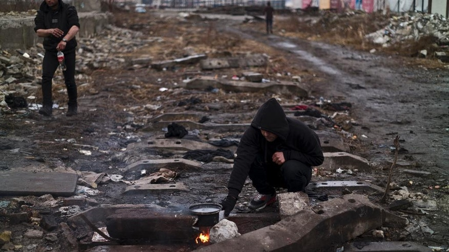 A migrant cooks on a fire outside an abandoned warehouse where he and other migrants took refuge in Belgrade, Serbia, Tuesday, Feb. 7, 2017. Hundreds of migrants have been sleeping rough in freezing conditions in central Belgrade looking for ways to cross the heavily guarded EU borders. (AP Photo/Muhammed Muheisen)
