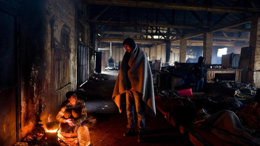 A migrant from Pakistan, center, talks with another while making tea on a fire in an abandoned warehouse where they took refuge in Belgrade, Serbia, Monday, Feb. 6, 2017. Hundreds of migrants have been sleeping rough in freezing conditions in central Belgrade looking for ways to cross the heavily guarded EU borders. (AP Photo/Muhammed Muheisen)