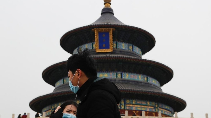 In this Tuesday, Feb. 7, 2017 photo, a couple wearing protection masks visits the Temple of Heaven in Beijing. Beijing has made robust efforts to retire aged vehicles and move heavily polluting industries to outlying provinces, yet the problem persists. The sheer size of the city's population, now at almost 22 million, and geographic conditions that surround it on three sides with smog-trapping mountains seem to require that further measures are needed. (AP Photo/Andy Wong)