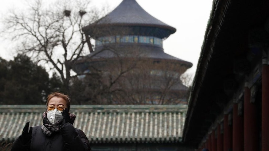 In this Tuesday, Feb. 7, 2017 photo, a Chinese woman wearing a mask for protection against air pollution performs an exercise at the Temple of Heaven in Beijing. Beijing has made robust efforts to retire aged vehicles and move heavily polluting industries to outlying provinces, yet the problem persists. The sheer size of the city's population, now at almost 22 million, and geographic conditions that surround it on three sides with smog-trapping mountains seem to require that further measures are needed. (AP Photo/Andy Wong)