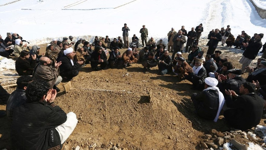 Villagers pray by the grave of a victim of a suicide attack on the Supreme Court in Kabul, Afghanistan, Wednesday, Feb. 8, 2017. A suicide bomber on Tuesday targeted the Supreme Court building in the Afghan capital, Kabul, killing at least 19 people. (AP Photo/Rahmat Gul)