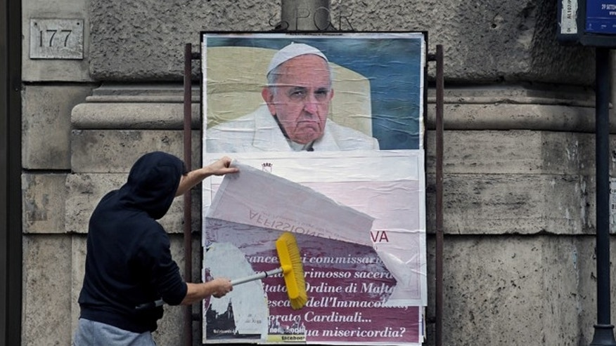 A worker covers a poster accusing the pope of attacking conservative Catholics in Rome, Italy, February 5, 2017