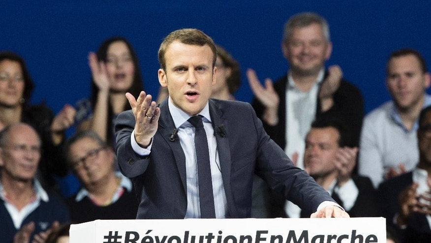 "FILE - In this Saturday, Dec. 10, 2016 file picture, former French Economy Minister and candidate for next year's presidential election, Emmanuel Macron gestures as he delivers his speech during a campaign meeting in Paris, France. ""Emmanuel Macron has humorously poo-pooed online chatter that he is having a gay affair. To hoots of laughter, the independent candidate this week delighted his supporters by making fun of rumors that he is leading a secret double life with a man."" (AP Photo/Kamil Zihnioglu, File)"