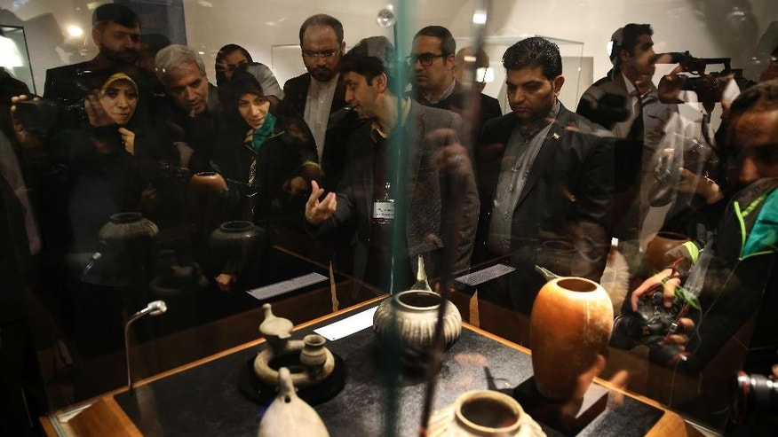 In this photo taken on Monday, Feb. 6, 2017, Special Assistant to the Iranian President on Citizenship Rights Elham Aminzadeh, left, and chief of Iran's Cultural Heritage, Handicrafts and Tourism Organization Zahra Ahmadipour, third left, listen to explanations from archaeologist Yousef Hassanzadeh during the opening of a show displaying some 550 ancient Persian artworks returned by Western countries, including the United States, at Iran National Museum in Tehran, Iran. (AP Photo/Vahid Salemi)