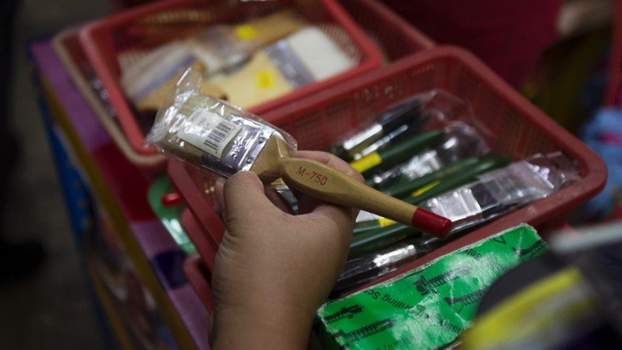 A domestic trade enforcement official checks on the paint brushes that are believed the brushes are made from pig bristles at a hardware store outside Kuala Lumpur, Malaysia on Wednesday, Feb. 8, 2017. Malaysian authorities have seized more than 2,000 paint brushes suspected to be made from pig bristles and sold without labels, in a crackdown following complaints from Muslim consumers. (AP Photo/Daniel Chan)