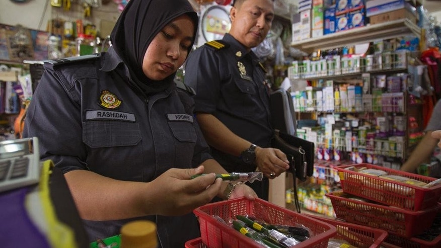 Domestic trade enforcement officers check on the paint brushes that are believed to be made from pig bristles at a hardware store outside Kuala Lumpur, Malaysia on Wednesday, Feb. 8, 2017. Malaysian authorities have seized more than 2,000 paint brushes suspected to be made from pig bristles and sold without labels, in a crackdown following complaints from Muslim consumers. (AP Photo/Daniel Chan)