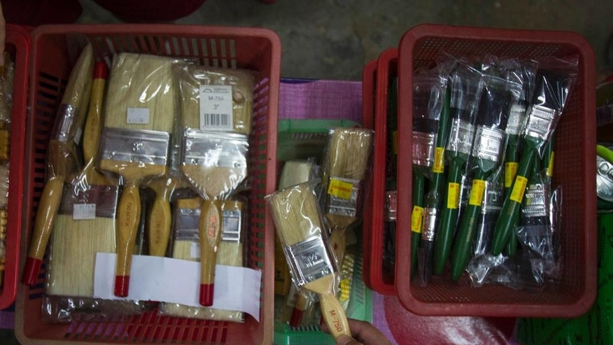 A domestic trade enforcement officer checks on the paint brushes that are believed to be made from pig bristles at a hardware store outside Kuala Lumpur, Malaysia on Wednesday, Feb. 8, 2017. Malaysian authorities have seized more than 2,000 paint brushes suspected to be made from pig bristles and sold without labels, in a crackdown following complaints from Muslim consumers. (AP Photo/Daniel Chan)