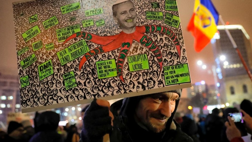 "A anti-government protester holds a poster depicting the leader of the ruling Social Democratic party Liviu Dragnea in Bucharest, Romania, Tuesday, Feb. 7, 2017. Romania's president told lawmakers Tuesday the country is in a ""fully-fledged"" political crisis, after hundreds of thousands demonstrated against a government measure that would weaken the country's anti-corruption drive. (AP Photo/Vadim Ghirda)"