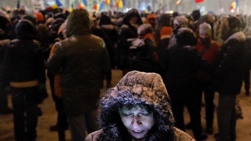 A woman looks at a mobile phone during a protest outside the government headquarters , in Bucharest, Romania, Wednesday, Feb. 8, 2017. Romania has seen massive anti-government protests in the week since the center-left government passed an emergency decree that would decriminalize some public corruption. (AP Photo/Vadim Ghirda)