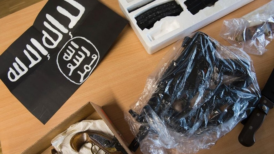 Seized weapons and an IS flag are on display during a news conference of the police in Goettingen, Germany, Thursday, Feb. 9, 2017. Twelve properties were searched in a raid in Goettingen.  Police in central Germany say they have detained two known Islamic extremists in an investigation of possible plans for an attack.   (Swn Pfoertner/dpa via AP)