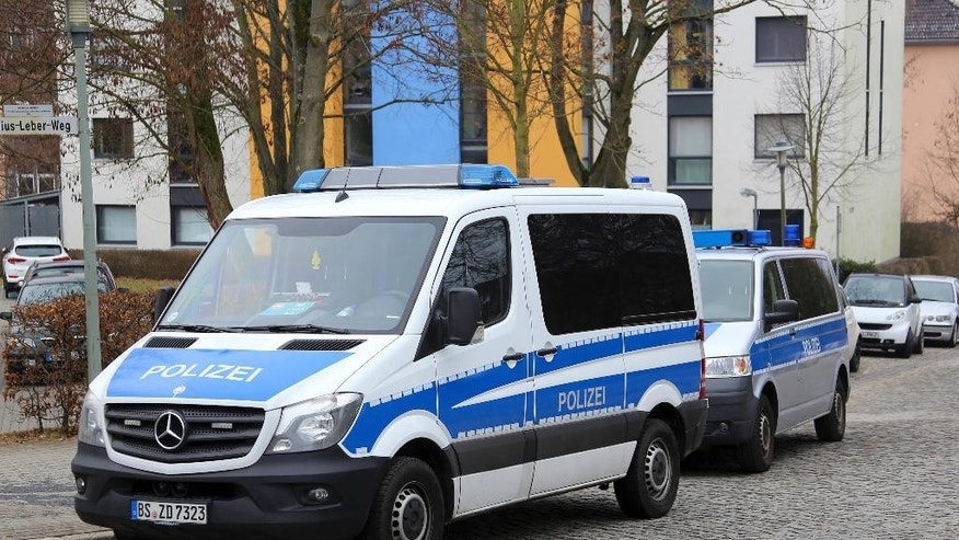 Police cars stand in front of apartment buildings after a raid in Goettingen, Germany, Thursday Feb. 9, 2017.  Twelve properties were searched in the operation. Police in central Germany say they have detained two known Islamic extremists in an investigation of possible plans for an attack.  (Stefan Rampfel/dpa via AP)