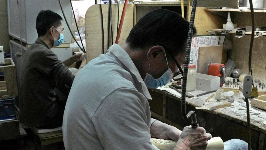 In this Jan. 13, 2017 photo, Wong Lai-ngan carves a mammoth tusk at the Lise Carving and Jewellrey workshop in Hong Kong. The decline of the city's once-flourishing ivory business is set to accelerate further after the Hong Kong and mainland Chinese governments unveiled plans in December to restrict local ivory trading. Wildlife activists hailed the news, saying that phasing out domestic markets is a key step in reducing demand for tusks fueling the illegal poaching decimating Africa's elephants. (AP Photo/Vincent Yu)