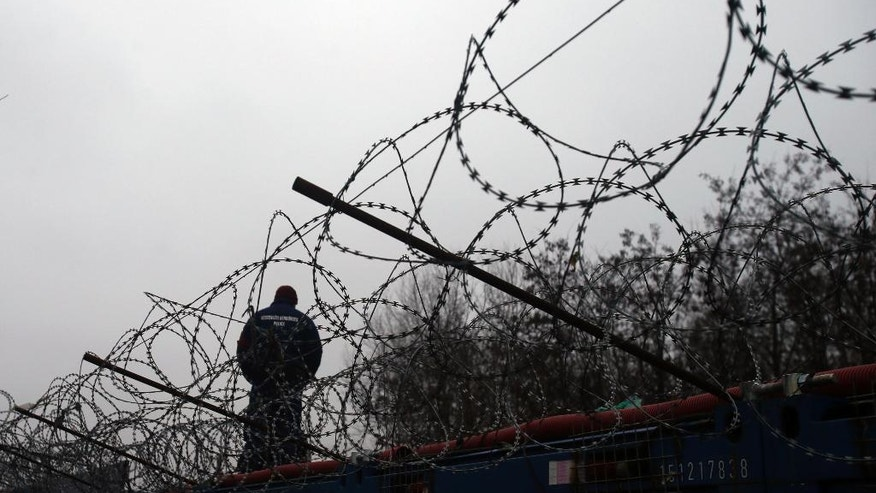 "A Hungarian police officer stands guard at Serbia's border with Hungary near a makeshift camp for migrants in Horgos, Serbia, Wednesday, Feb. 8, 2017. European Commission Vice-President Frans Timmermans said Wednesday that it is ""highly urgent"" for countries to live up to their pledges, with the legally binding scheme set to expire in September. (AP Photo/Darko Vojinovic)"