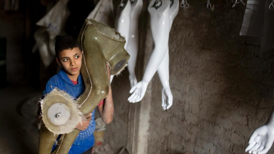 In this picture taken Wednesday, Jan. 18, 2017, a young worker carries a fiberglass mannequin at a workshop at Al-Kharqaniyah village, in Egyptian province of Qalyubia, just outside Cairo, Egypt. There is an unlikely industry thriving in an unlikely place: Making mannequins in the village north of Egypt's capital, Cairo. The use of mannequins in Egypt dates back to the early years of the last century, when Jewish-owned department stores imported them to display the western attire they sold to expatriates and wealthy Egyptians. (AP Photo/Amr Nabil)