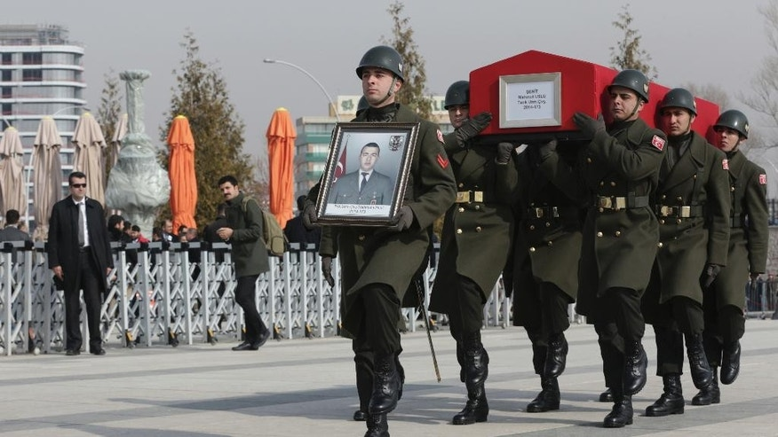 Military honour guard carry the coffin of Mahmut Uslu, one of five Turkish soldiers killed in an attack by IS militants around the Syrian town al Bab on Tuesday, during a ceremony in Ankara, Turkey, Thursday, Feb. 9, 2017. (AP Photo/Burhan Ozbilici)