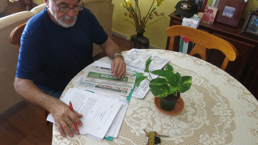 In this Feb. 8, 2017 photo, Juan Camacho reviews documents as part of his new job as a second-grade teacher's assistant in San Juan, Puerto Rico. Camacho thought he would visit Spain, take a university literature course and get to sleep in more when he retired after nearly four decades as a teacher. Instead, the 70-year-old is working to supplement his pension. (AP Photo/Danica Coto)
