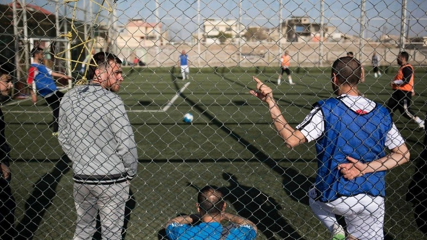 In this Wednesday, Feb. 8, 2017 photo, Mosul residents play soccer on a pitch in the liberated eastern part of the city. The pitch was closed for months due to heavy fighting between Iraqi forces and Islamic State militants, but was reopened recently as daily life slowly returns in Iraq's second largest city. (AP Photo/Bram Janssen)