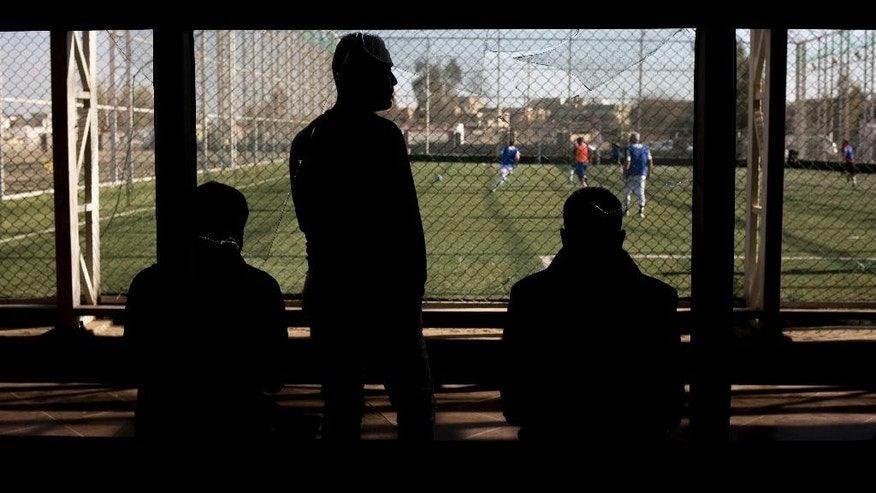In this Wednesday, Feb. 8, 2017 photo, spectators watch in front of a window broken in lashes between Iraqi forces and Islamic State militants, as other Mosul residents play soccer on a pitch in eastern Mosul. The pitch was closed for months due to heavy fighting, but was reopened recently as daily life slowly returns to in the city. (AP Photo/Bram Janssen)