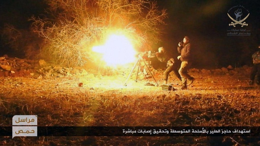 "This photo released online on Thursday, Feb. 9, 2017, by the website of the al-Qaida-linked Fatah al-Sham, an anti-government militant group, shows fighters from the al-Qaida-linked Fatah al-Sham Front, attacking the government's Tayr checkpoint in the Homs province, Syria. The war's January toll – some 2,000 dead, about a third of them civilians, according to the Britain-based Syrian Observatory for Human Rights monitoring group – is the lowest it has been in four years, but that may be because the government wrapped up operations for Aleppo, the country's largest city, last year. Arabic, bottom, reads: ""Targeting the Tayr checkpoint with medium weapons, causing injuries."" (Fatah al-Sham via AP)"