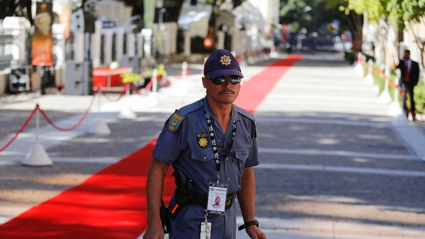 A South African policeman provides security next to the red carpet at parliament in Cape Town, South Africa, Thursday, Feb. 9, 2017. South African police and military forces are deploying ahead of a speech in parliament by President Jacob Zuma, the target of protesters who say he should quit because of corruption allegations. (AP/hoto/Schalk van Zuydam)