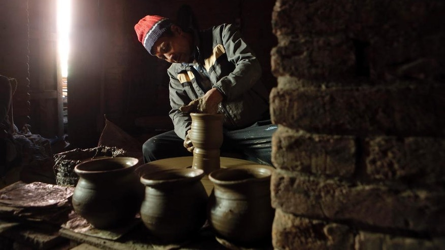 "In this Saturday, Jan. 28, 2017 photo, Nepalese Prajapati potter Dil Krishna Prajapati, 54, moulds a clay pot in the ancient Nepali town of Thimi. As more young people leave town for better paying jobs in other parts of Nepal or abroad, fewer families have to eke out an income from the relatively low-returns business of clay pottery. ""Times have changed, new products have flooded the market, and people from potter caste love other lucrative professions. I fear that the tradition will fade away,"" said Dil Krishna. (AP Photo/Niranjan Shrestha)"