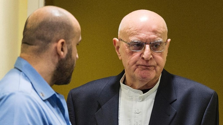 FILE - In this Jan. 30, 2015 file picture Ljubisa Beara, right, enters the courtroom of the International Criminal Tribunal for the former Yugoslavia (ICTY) in The Hague, Netherlands. The Bosnian Serb commander convicted of war crimes over the 1995 Srebrenica massacre has died in a German prison. He was 77. A spokeswoman for Berlin state's justice department told The Associated Press on Friday Feb. 10, 2017 that Ljubisa Beara died Feb. 8.   (AP Photo/Michael Kooren, Pool, file )