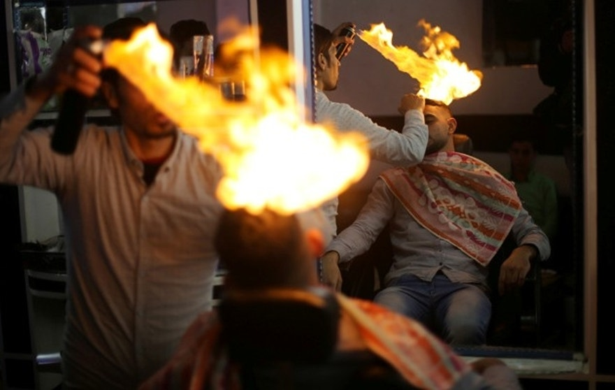 Palestinian barber Ramadan Odwan styles and straightens the hair of a customer with fire at his salon in Rafah, in the southern Gaza Strip February 2, 2017. Picture taken February 2, 2017.   REUTERS/Ibraheem Abu Mustafa - RTX309NS
