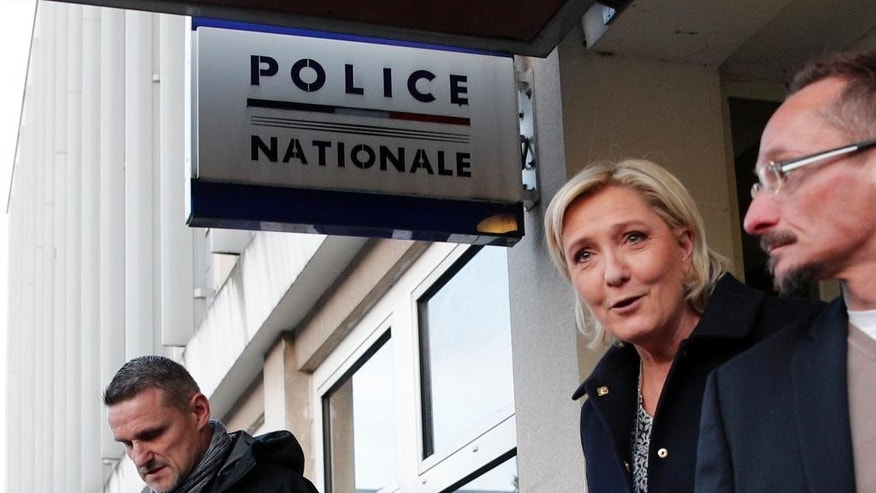 French far-right presidential candidate Marine Le Pen leaves after a meeting at the Juvisy-sur-Orge police station, south of Paris, France, as she campaigns for the upcoming presidential election, Tuesday, Feb. 7, 2017. (AP Photo/Christophe Ena)
